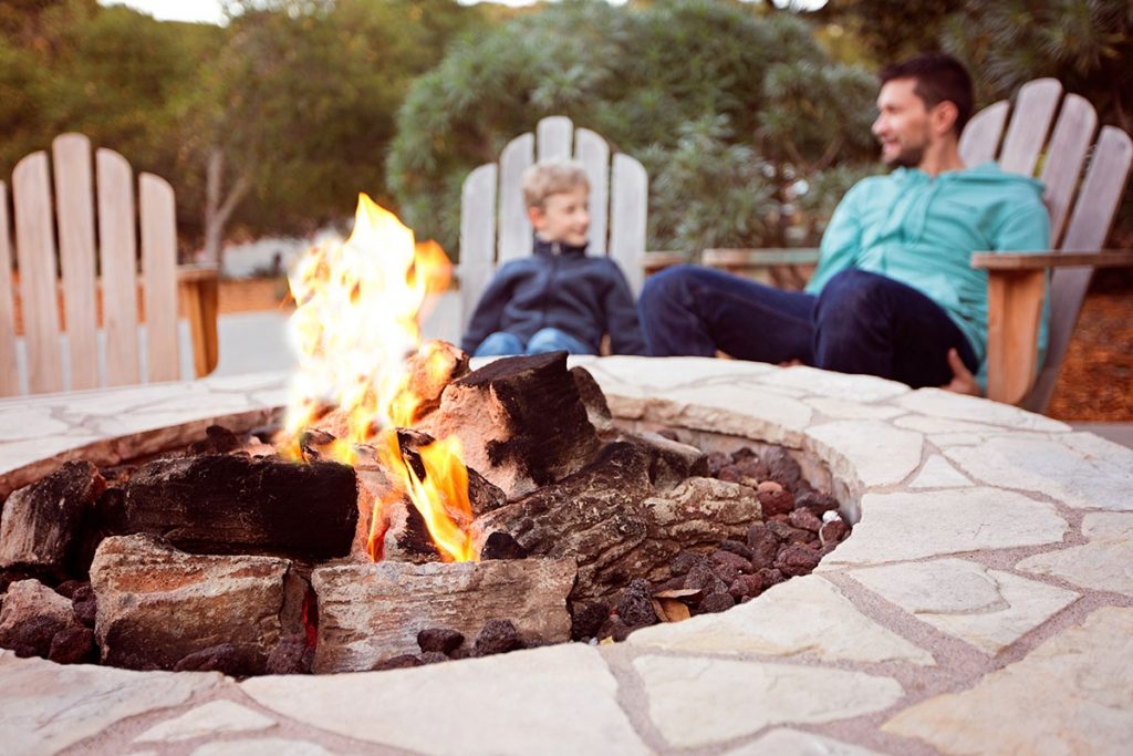 Father and son sitting by a firepit