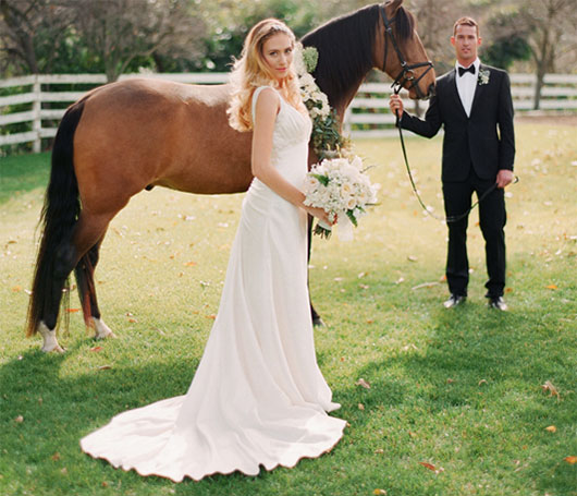 Husband and wife posing for wedding photo with one of Roaring Brook Ranch's horses