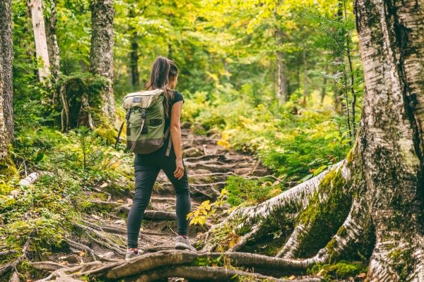 Girl with backpack hiking in heavily wooded area